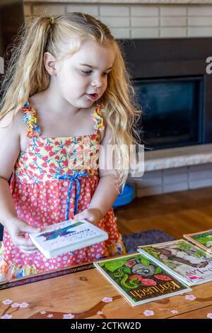 Die 3-jährige Lily hat ein Buch zum Lesen ausgewählt - Stockfoto