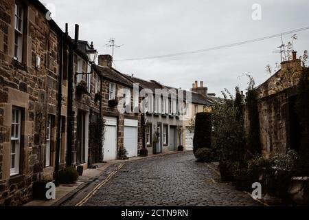 Perspektivischer Blick auf die alte schmale Straße mit grunge Wohngebäuden Auf dem Hintergrund des grauen Himmels in den schottischen Highlands