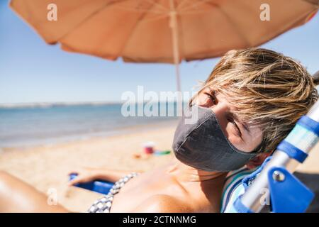 Porträt einer Frau mit Gesichtsmaske im Sommer Urlaub in der Sonne auf einer Liege rechts liegen Neben einem orangefarbenen Schirm in der Mitte eines coron - Stockfoto