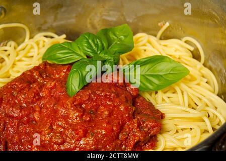 Fügen Sie Bolognese Sauce auf Spaghetti in Topf. Kochen Pasta Bolognese zu Hause - Stockfoto
