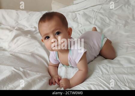 Ein sechs Monate altes Baby in hellrosa kriecht auf dem weißen Bett. - Stockfoto