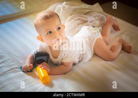 Kleines Baby 8 Monate liegt auf einem weißen Bett. Kleinkind Mädchen spielt mit der Action-Kamera und Blick auf Mama - Stockfoto