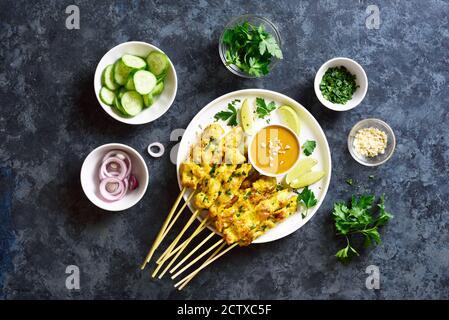 Hähnchen-Satay mit Erdnusssauce. Gegrillte Hähnchenspieße mit Erdnussdipping-Sauce. Leckeres Essen zum Abendessen oder Party Vorspeisen. Blaue Steinrückung