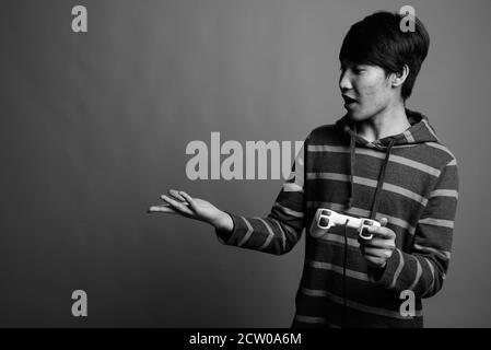 Jungen asiatischen Mann spielt Spiele gegen grauer Hintergrund