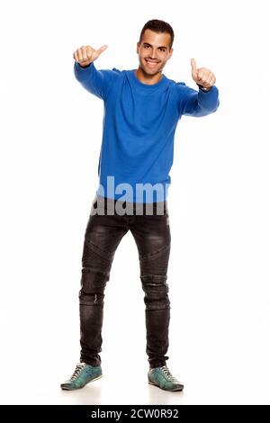 Schöner glücklicher junger Mann in Bluse und Jeans auf weiß Hintergrund zeigt Daumen nach oben - Stockfoto