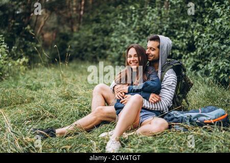 Frau mit langen Haaren und Mann auf dem Gras im Wald mit Rucksäcken sitzen. Viel Spaß in der Natur, Umarmung und Küssen.