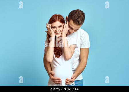 Schwangere Frau in weißem T-Shirt und Mann verheiratet Paar warten Für Baby blauen Hintergrund abgeschnitten Ansicht der Emotionen - Stockfoto