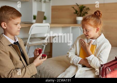 Adorable Kinder in der Liebe, Junge machen Vorschlag, Rotschopf Mädchen, gehen zu heiraten, verhalten sich wie Erwachsene Stockfoto