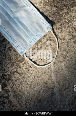 Es wurde eine auf dem Boden verlorene medizinische Schutzmaske verwendet. Einwegmaske liegt auf der Straße. Falsche Entsorgung der verwendeten Gesichtsmaske