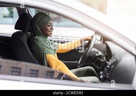 Probefahrt. Black Muslim Lady Fahren Auto In Der Stadt, Check New Auto Stockfoto