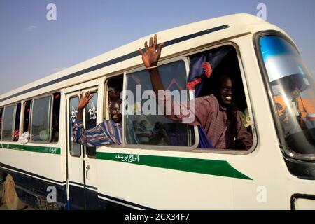 Intern Vertriebene Menschen Welle zu ihren Verwandten aus einem Bus in einen Transport-Konvoi für Einheit Bundesstaat im Südsudan, in Khartum 28. Oktober 2010 gebunden. Sudans Nord-Süd-Bürgerkrieg, der längste Bürgerkrieg Afrikas war, entsteint Khartums islamistische Regierung gegen die Rebellen, die vor allem Christentum und traditionellen Glauben zu folgen, und gipfelte in einem Friedensabkommen von 2005 Nord-Süd. Diese Flüchtlinge haben im Nord-Sudan seit 21 Jahren gelebt. REUTERS/Mohamed Nureldin Abdallah (SUDAN - Tags: Politik-Gesellschaft-TRANSPORT)