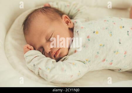 Neugeborenes Baby in weißen warmen Kleidern schlafen völlig im Bett Entspannt und sicher fühlen - Stockfoto