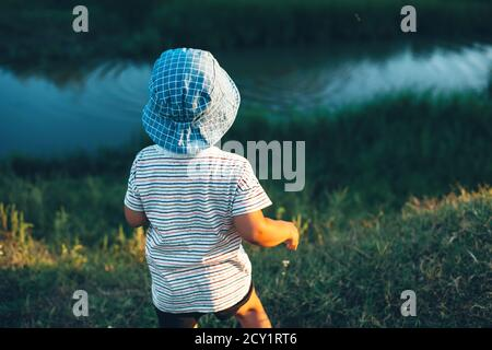 Kaukasischer Junge, der auf einen kleinen Fluss schaut und Steine wirft Trägt einen blauen Hut in einem grünen Feld