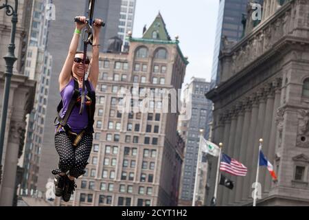 """Eine Frau fährt eine Seilrutsche durch die Straßen von Manhattan in New York Citys """"Summer Streets"""" Initiative in New York, 11. August 2012. Das Programm, das in seinem fünften Jahr, lädt die Öffentlichkeit zur Teilnahme an verschiedenen Aktivitäten wie Fahrradfahren, Klettern und Seilrutschen, geschlossenen Straßen in ganz Manhattan von der Brooklyn Bridge zum Central Park. REUTERS/Andrew Burton (Vereinigte Staaten - Tags: Gesellschaft) Stockfoto"""