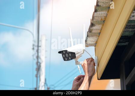 Techniker installieren eine drahtlose CCTV-Kamera an der Vorderseite des Hauses, um die Sicherheit zu gewährleisten. - Stockfoto