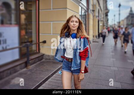 Junge kaukasische Frau auf überfüllten Straße im Zentrum der europäischen Stadt am Ende des Sommertages. Weiße Frau im Freien in Menschenmenge. Russische Mädchen läuft Stockfoto