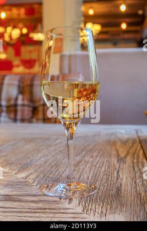 Ein Glas Weißwein steht auf einem Tisch mit einer Holzfläche in einem Café. Vertikale Ausrichtung, selektiver Fokus, unscharfer Hintergrund.
