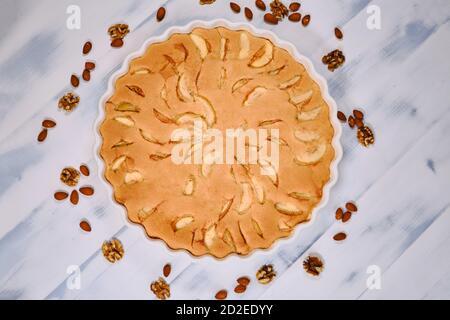 Apfelkuchen mit Nüssen, Draufsicht. Hausgemachte Kuchen reife Äpfel auf weißem Holz Hintergrund. Obstkuchen mit Mandeln und Walnüssen. Stockfoto