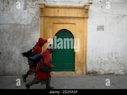 Zwei Wasserverkäufer gehen bei Sonnenaufgang in der Altstadt von Rabat an einer hölzernen Tür vorbei, auf diesem Bild, das am 3. April 2009 aufgenommen wurde. REUTERS/Steve Crisp (MAROKKO GESELLSCHAFT REISEN)