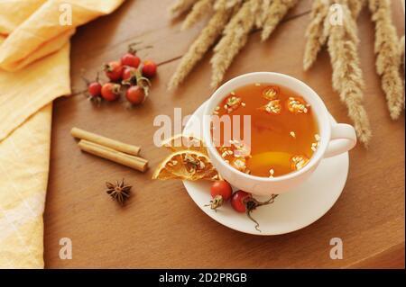 Gesunde Herbst Vitamin-Tee Hagebutten Beeren, Zitrone und Zimt auf Holztisch mit Bouquet von getrockneten Blumen und Baumwolle Serviette, gemütlich wärmende Tee Teil - Stockfoto