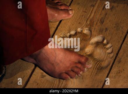 Die Füße des Mönchs Hua Chi sind in der Nähe die Fußabdrücke von ihm gemacht, indem Sie beten an der gleichen Stelle seit Jahrzehnten in einem Kloster in der Nähe von Tongren, Qinghai Provinz 25. Februar 2009 gesehen. Hua Chi, wer, dass er etwa 70 Jahre alt ist glaubt, hat an der gleichen Stelle betete so viele Male, dass perfekte Fußabdrücke auf der hölzernen Tür bleiben. Der Mönch und Arzt der traditionellen Medizin wurde in den kleinen Tempel in der Kloster-Stadt Tongren in Chinas westliche Qinghai Provinz seit fast zwanzig Jahren zu eine strengen persönlichen Ritual durchzuführen, kommen. Jeden Tag kommt vor Sonnenaufgang, Hua Tempel di Spagna, Platzierung