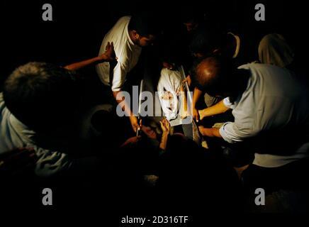 Menschen begraben den Körper eines palästinensischen Kindes Yehya Abu Gazal, der getötet wurde, nachdem israelische Soldaten beschossen Figuren, die sie in der Nähe von Raketenwerfern, im nördlichen Gazastreifen 29. August 2007 entdeckt.  REUTERS/Suhaib Salem (GAZA) Stockfoto