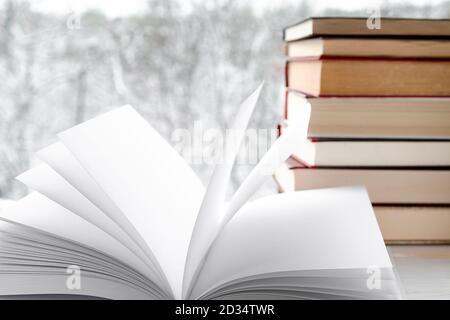 Weiße saubere Seiten des offenen Buches vor dem Hintergrund der Alte Bücher und Winterwald