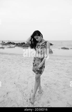 Junge schöne asiatische Frau unten und schauen, Spielen mit dem Sand am öffentlichen Strand von Hua Hin in Thailand