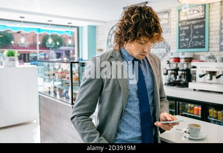 Geschäftsmann, der in einem Café mobil aussieht - Stockfoto