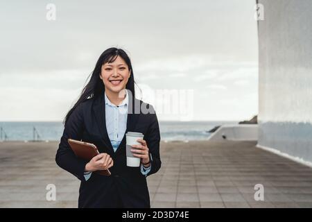 Asiatische Geschäftsfrau hält intelligente Tablette und trinken mitnehmen Kaffee außerhalb Büro - Entrepreneurship professionelle Job-Konzept