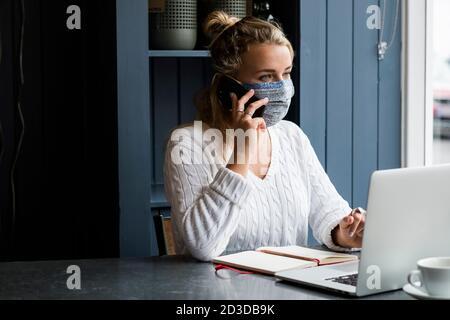 Junge blonde Frau trägt Gesichtsmaske allein sitzen an einem Café-Tisch mit einem Laptop-Computer, mit Handy, arbeiten aus der Ferne. - Stockfoto