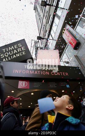 """Ein kleiner Junge sucht vom Gehsteig wie Konfetti aus einem Fenster über den Times Square während der jährlichen """"Luft Würdigkeit Test"""" von der Konfetti verwendet für die Times Square 2005 Silvester Feier in New York City, 29. Dezember 2004 geworfen wird. Dreitausend Pfund von Konfetti aus verschiedenen Gebäuden um Mitternacht am Silvesterabend entfällt bei die Tausenden Times Square packen, den jährlichen """"Ball Drop"""" als 2004 Pässe in 2005 zu sehen. REUTERS/Mike Segar MS/SV - Stockfoto"""