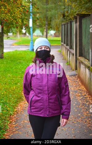 Junge Frau in warmen Kleidern tragen lila Jacke mit schwarzen wiederverwendbaren Gesichtsmaske und stricken Hut stehen auf Bürgersteig mit braunen Blättern bedeckt. Herbst - Stockfoto
