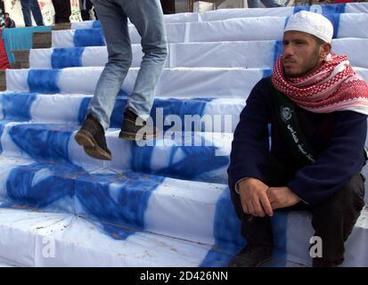 Ein Anhänger der islamischen militanten Gruppe Hamas geht einige Schritte mit einer israelischen Flagge bedeckt, während ein anderer Unterstützer auf den Beginn der Kundgebung zum 13. Jahrestag der Gründung der Hamas in Gaza-Stadt am 15. Dezember 2000 wartet. Der Hamas-Gründer Sheikh Salah Shehada schwor am Freitag, seinen bewaffneten Kampf gegen die israelische Besetzung des Westjordanlandes und des Gazastreifens fortzusetzen. AJ/AA