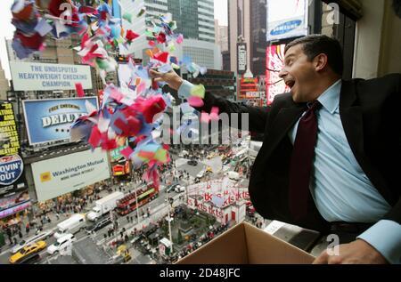 """Tim Tompkins, Präsident der Times Square Alliance, wirft Konfetti aus einem Fenster über den Times Square während ihrer jährlichen """"Würdigkeit auf Luftdichtigkeit"""" von der Konfetti verwendet für die Times Square 2005 Silvester Feier in New York City, 29. Dezember 2004. Dreitausend Pfund von Konfetti aus verschiedenen Gebäuden um Mitternacht am Silvesterabend entfällt bei die Tausenden Times Square packen, den jährlichen """"Ball Drop"""" als 2004 Pässe in 2005 zu sehen. REUTERS/Mike Segar MS/SV - Stockfoto"""