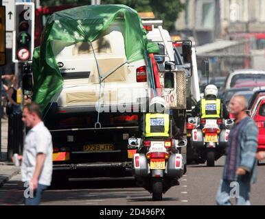 Eine Erholung LKW mit einer Polizei-Eskorte dauert einen überdachte van von der Website der explodierten Bus vom oberen Woburn Place im Zentrum von London, 10. Juli 2005. Drei Männer am Sonntag am Londoner Flughafen Heathrow unter Anti-Terror-Gesetze verhaftet wurden, teilte die Polizei mit. REUTERS/Francois Lenoir RS/RD/DY