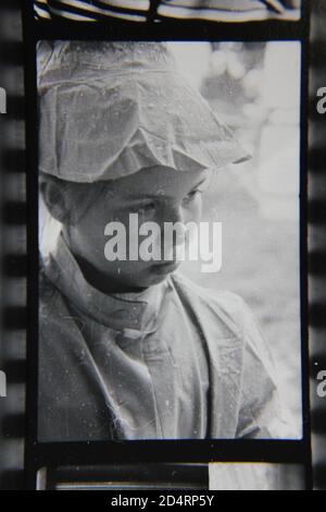 Feine 70er Jahre Vintage Schwarz-Weiß-Fotografie eines jungen absentminded Mädchen trägt einen lustigen Hut. - Stockfoto