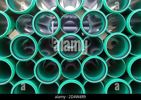 Seitenansicht eines Stapels grüner Kunststoffrohre für Straßenbau - Stockfoto