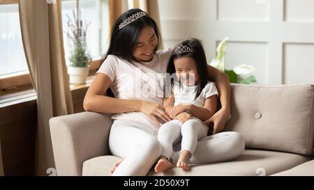 Glücklich asiatische Mutter und kleine Tochter kitzeln, Spaß haben