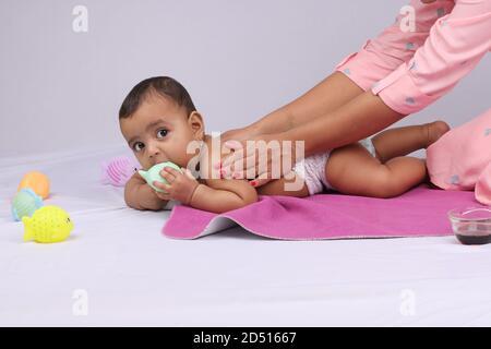 Indische Mutter massiert ihr schönes Baby.
