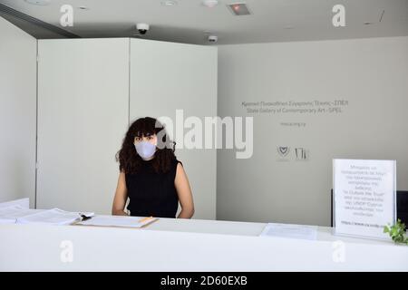 """Junge Frau trägt Gesichtsmaske für covid Vorsichtsmaßnahmen an der Rezeption in """"State Gallery of Contemporary Art"""", Pafos, Zypern - Stockfoto"""