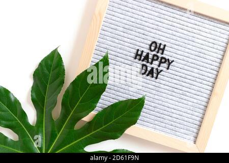 Komposition mit Aralienblatt und Briefbogen mit Zitat Oh happy Tag