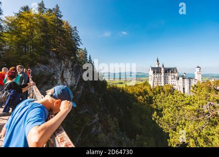 Fussen, Deutschland - 27. SEPTEMBER 2014: Die Menschen genießen einen wunderschönen Blick auf das weltberühmte Schloss Neuschwanstein, den neuromanischen freund aus dem 19. Jahrhundert - Stockfoto