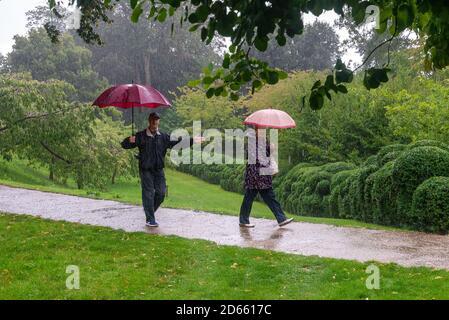 Paar im Regen mit Regenschirmen, tanzt er im Regen Stockfoto