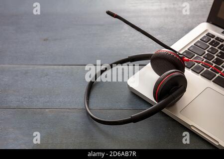 Kundendienst, Helpdesk, Kommunikation. Call Center- und Home Office-Konzept. Headset und Laptop auf blauem Holzschreibtisch, Nahaufnahme, Kopie sp Stockfoto