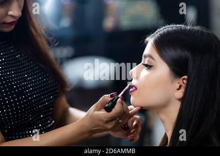 Ein junges indisches Modell in einem Schönheitssalon, Make-up-Künstler Anwendung Lippenstift auf Kunden.