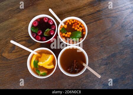 Winter süß wärmend alkoholische, alkoholfreie Getränke auf Holztisch. Glühwein mit Honig, Sanddorn, Kirschen, Preiselbeeren, Sternanis, Minze, - Stockfoto