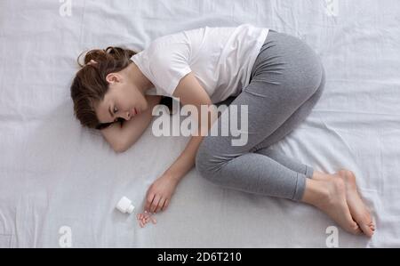 Junge hoffnungslose Frau im Bett liegend mit Glas Pillen, Draufsicht - Stockfoto