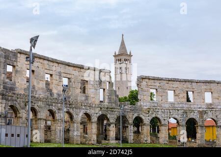 Blick auf den Glockenturm der Kirche und das Kloster des Heiligen Antonius von den Mauern des ikonischen antiken römischen Amphitheaters in Pula, Istrien, Kroatien