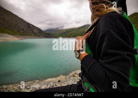 Frau, die nach dem Sporttraining Pause nimmt. Sie steht mit ihren Händen auf Hüften und schaut an bewölkten Tagen auf den klaren See. Weibliche Athletin trägt ein Stockfoto